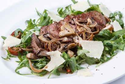 Beef tagliata with arugula and mushrooms