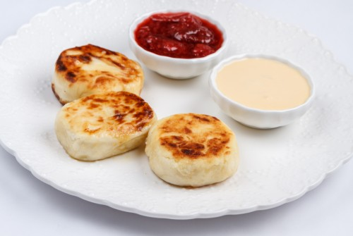Rustic cottage cheese syrniki with custard and strawberry sauce
